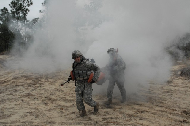 Sgt. 1st Class Chris Patterson, Company B, 832nd Ordnance Battalion, Redstone Arsenal, Ala., and a fellow squad member emerge from smoke carrying a simulated injured Soldier to an extraction point during Tuesday's field-training exercise for the AIT Platoon Sergeant's Course.