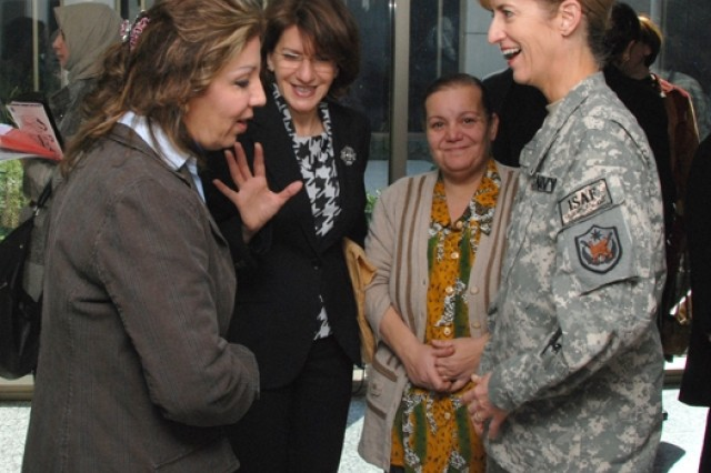 """Dr. Nada Ibrahim (left), member of the Iraqi Parliament; Azza Humadi, program manager of the Gulf Region Division's Women's Advocate Initiative; an unidentified conference attendee; and Rear Adm. Kathleen Dussault, commander, Joint Contract Command, Iraq and Afghanistan, enjoy a moment during a break Jan. 12 at the """"Women's Business Day"""" conference at the Al Rasheed Hotel in Baghdad's International Zone."""