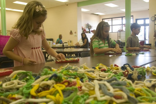 SCHOFIELD BARRACKS, Hawaii - (Left to right) Natalie Pressell, 7, Tia Johnson, 10, and Brenner Kemper, 7, weave potholders during a day at Keiki Craft Camp. The four-day camp presented an array of creative projects for young keiki at the Arts & Crafts Center on Schofield Barracks.