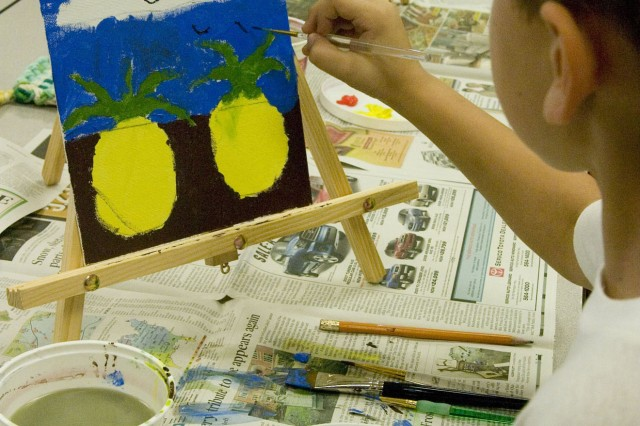 SCHOFIELD BARRACKS, Hawaii - Brightly colored pineapples fill the canvas as Brenner Kemper, 7, puts finishing touches on his painting during the camp. The four-day Keiki Craft Camp presented an array of creative projects for young keiki at the Arts & Crafts Center on Schofield Barracks.