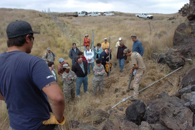 POHAKULOA TRAINING AREA, Hawaii - Joel Brunger (right forefront), fence crew leader, demonstrates to Col. Maria Gervais (center, wearing beret), commander, Army Environmental Command, and staff how the fence post pounder is used to insert fence posts into lava-hardened grounds at PTA's borders, known as the western fuel break.