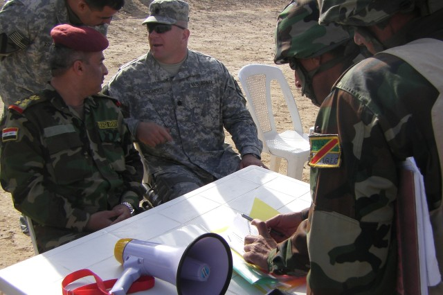 """Soldiers from the 41/10th IA Div. sign pledges of loyalty to their unit and country, with Iraqi Brig. Gen. Muhammad and Lt. Col. Timothy Daugherty, commander of the 5th Bn., 82nd FA Regt., 4th BCT, 1st Cav. Div. at the Besmaya Range Complex Jan. 14."""""""