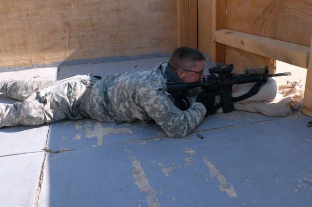 """Staff Sgt. Michael Lashua, from Walker, La., a cavalry scout and squad designated marksman with Troop B, 4th Squadron, 9th Cavalry Regiment, 2nd Brigade Combat Team, 1st Cavalry Division, prepares to fire his M-4 rifle from the top floor of a building while zeroing his weapon at a firing range near Camp Buehring, Kuwait Jan. 14. """""""