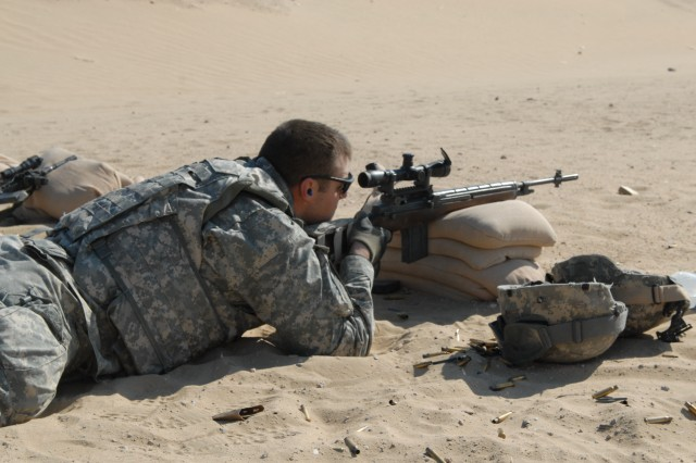 """Chicago native Spc. Stephen Battisto, a cavalry scout and squad designated marksman with Troop C, 4th Squadron, 9th Cavalry Regiment, 2nd Brigade Combat Team, 1st Cavalry Division, steadies his aim while zeroing his M-14 rifle at a rifle range near Camp Buehring, Kuwait Jan. 14. """""""
