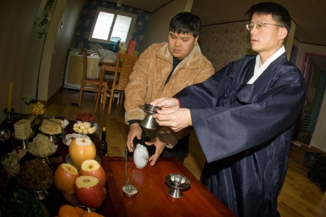 Lee Hoo-jeong (right) and family members honor their ancestors with a traditional Korean ceremony during the Lunar New Year.