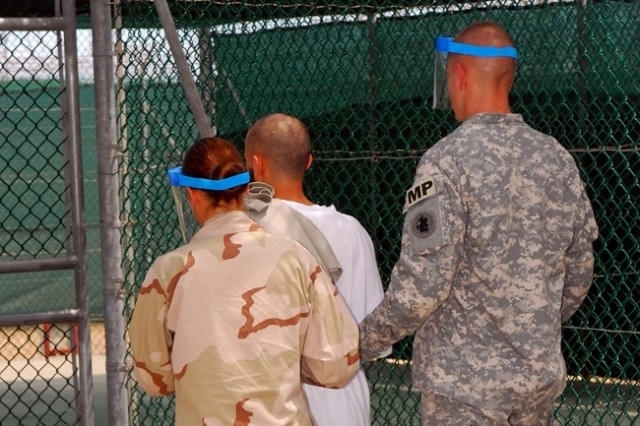 Army and Navy guards escort a detainee to recreational area Camp One at Joint Task Force Guantanamo Bay, Cuba.