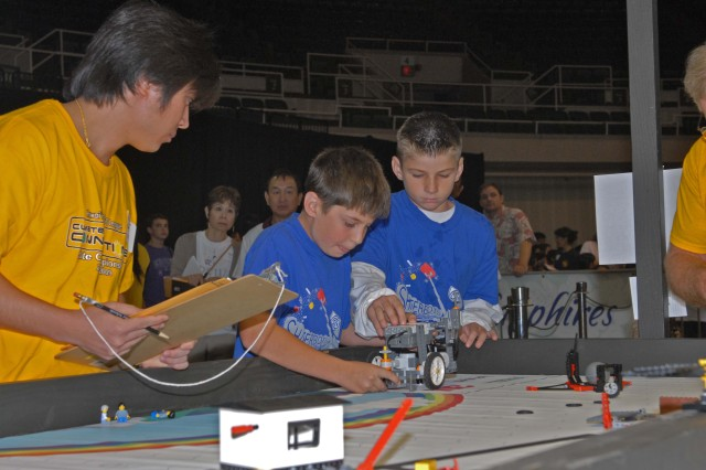 Ft. Shafter, Hawaii - Shafter Elementary's Scott Greene, 11 (left) and Kyle Bender, 10 (right) make adjustments to their robot as a judge looks on during the Hawai'i FIRST LEGO® League State Championship Tournament which was held at the Neal S. Blaisdell Arena in Honolulu.
