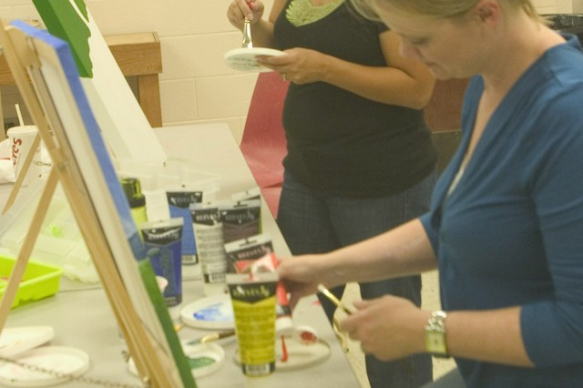 SCHOFIELD BARRACKS, Hawaii - Family member Heather Brock (front) and art instructor Nikki Mizak mix paint for their ongoing art project during the Thursday night adult acrylic painting class.