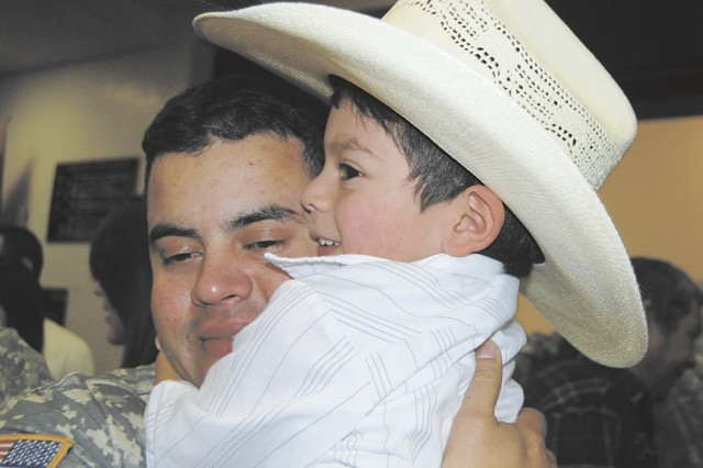"""Staff Sgt. Jorge Perez Sr., gets a big hug from his son, Jorge Jr., 3 years old at the welcome home ceremony Jan.15 for the 591st Medical Logistics Company."""""""