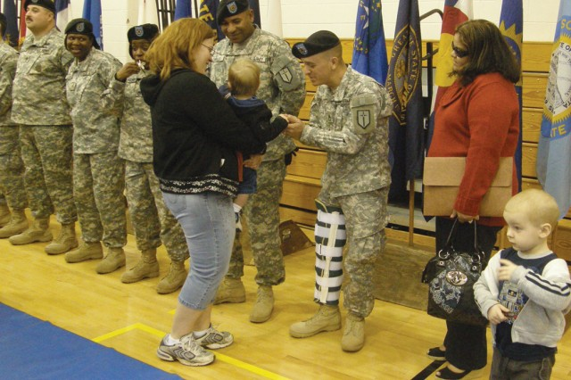 Lydia Fessenden helps her son Ethan, 1, shake hands with a Soldier from the 142nd Combat Sustainment Support Battalion, 1st Maneuver Enhancement Brigade, at its redeployment ceremony Jan. 15