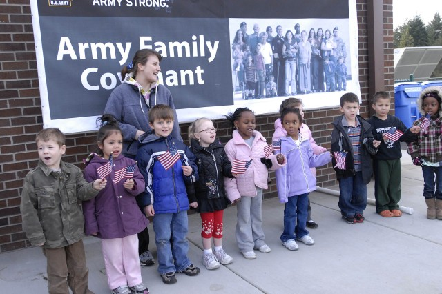 """Ten children from Madigan Child Development Center sang 'Grand Old Flag"""" during the CDC dedication ceremony of the Eileen Beaulieu Infant Toddler Center Jan. 14.  Darcy Eoff, Child and Program assistant, helps the children with their song."""