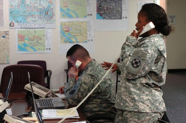 2nd Lt. LaCandice Johnson and Spc. David South, 49th Trans. Bn., 15th SB, 13th ESC, talk to participants in the 56th Presidential Inauguration Jan. 18. The Soldiers were part of the Movement Control Center with the Armed Forces Inaugural Committee and managed the transportation for the ceremony and parade participants.