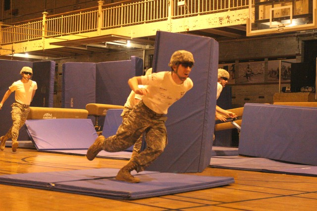 Cadets dash to scale a wall during the Military Movement Assault Course Brigade Open Jan. 14 in Hayes Gymnasium. During the quick burst, cadets must avoid getting hit by tennis balls, or direct fire, that would eliminate them from the competition.