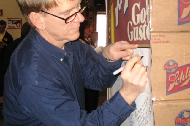 Mr. Jim Freeland, Corporate Chef, Principal for Lou Malnati's, signs a wall-sized troop greeting card at Lou Malnati's corporate office in Chicago, Ill. January 23, 2009 before shipping two crates of Schlitz beer and a truck-load of pizza to Soldiers in Iraq and Afghanistan for Super Bowl XLIII.