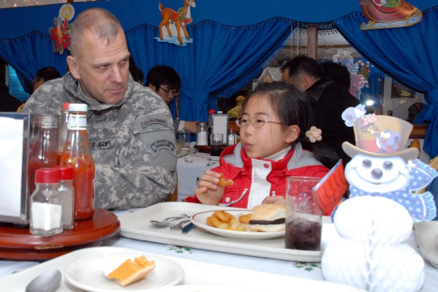 Maj. Steven Briggs, physician assistant at UNCSB-JSA, chats with a student during lunch at Camp Bonifas\' dining facility minutes prior to Santa's visit Dec. 23.