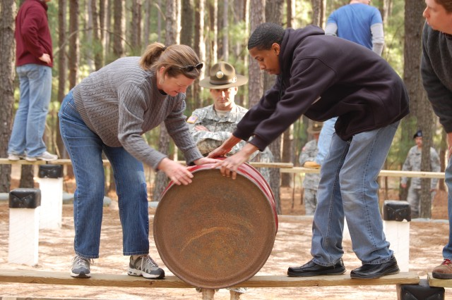 Susan McCants and Carlton Boyd navigate a barrel across a plank under the watchful eyes of Staff Sgt. Michael Williams, Drill Sergeant School.