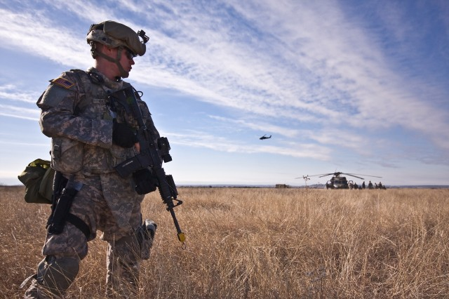 "Baltimore native Pfc. John Dixon, a Soldier in Company F, 3rd Assault Helicopter Battalion, 227th Aviation Regiment, 1st Air Cavalry Brigade, 1st Cavalry Division, guards the perimeter as other Blues Platoon Soldiers tend to wounded aircrew members during a training exercise Jan. 15 on Fort Hood, Texas. The term ""Blues Platoon"" is used in reference to ground forces who are attached to aviation units."