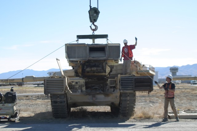Hand signals are used between employees and crane operators with directions when maneuvering around the M-1 Abrams.