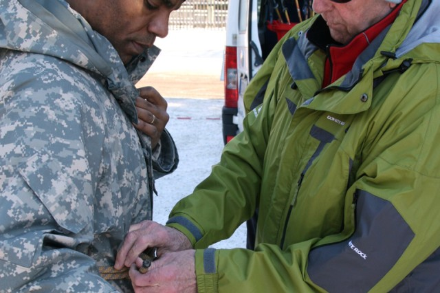 A ski instructor helps Command Sgt. Maj. James Esters, U.S. Army Garrison Ansbach, Germany, suit up for an Alpine ski tour Jan. 12 in Garmisch during a test run for Installation Management Command-Europe's Warrior Adventure Quest program. The one-day event took about 30 Soldiers from the 12th Combat Aviation Brigade and a handful of garrison staff members to Garmisch for a day of Alpine skiing and snowshoeing.