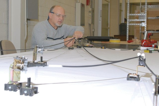 Paul Dmuchoski, electronics mechanic, lays out the Crows II cable assembly on the new wiring harness tables. ""