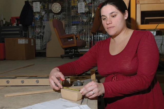 Erin Moran, mechanical engineer, Production Engineering Directorate, verifies mounting bracket dimensions.  These brackets are part of a mounting assembly for securing generators on van trailers.