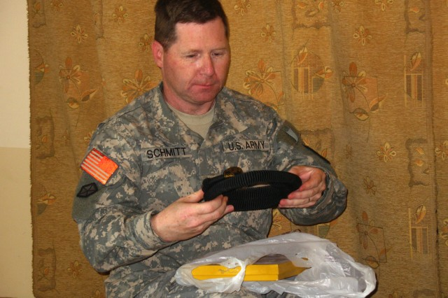 """287th Sustainment Brigade commander Col. Robert Schmitt admires the gifts of an """"agal"""" (plaited cord) and """"kaffiyeh"""" (scarf) given to him by Shaykh Tayseer Mohammed Al-Marshad at a dinner honoring 287th Sust. Bde. leaders on Jan. 21 at Al-Marshad's home in Dhi Qar province.  (U.S. Army photo by Master Sgt. Carl Mar)"""