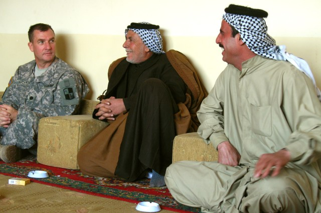 Lt. Col. Clint Moyer, chief of 287th Sustainment Brigade Civilian Military Operations, enjoy after-dinner conversation with Al Batha District Councilman Mohammed Tayieh and their host, Shaykh Tayseer Mohammed Al-Marshad of the Al Ghizi Tribe, Jan. 21. (U.S. Army photo by Master Sgt. Carl Mar)