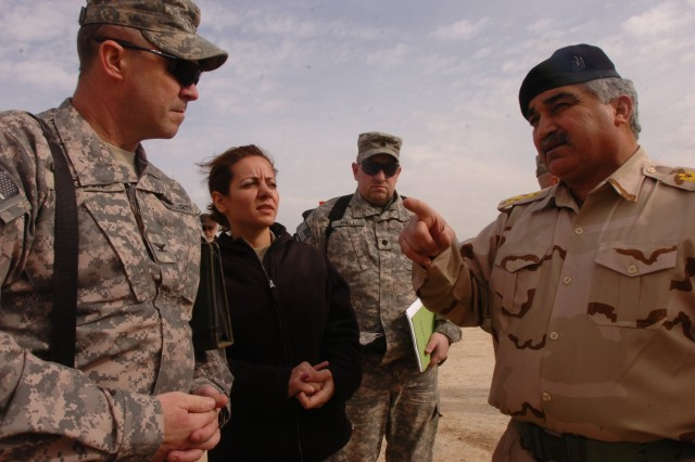 (Left) Col. Curt Higdon, the G-3 operations officer for the 3rd Sustainment Command (Expeditionary), and (right) Brig. Gen. Mohammedali Kathem, Ammunition Director for the Iraqi Army, talk about the IA's ammunition process with the help of an interpreter at the Bayji National Ammunition Depot Jan. 26.