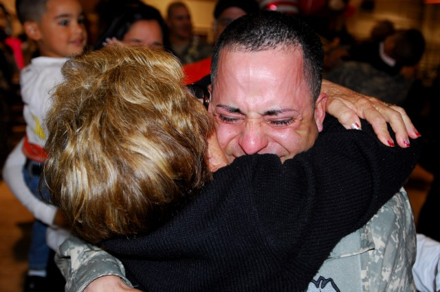 Sgt. Jaime Toro is overcome with emotion as he hugs his mother-in-law Julia at a redeployment ceremony early Tuesday morning, Jan. 27 at Wheeler Army Airfield, Hawaii.  Toro, with the 2nd Stryker Brigade Combat Team was one of more than 180 Soldiers who returned from a 15-month deployment to Iraq.  Soldiers from the 728th Military Police Battalion also returned Tuesday morning.