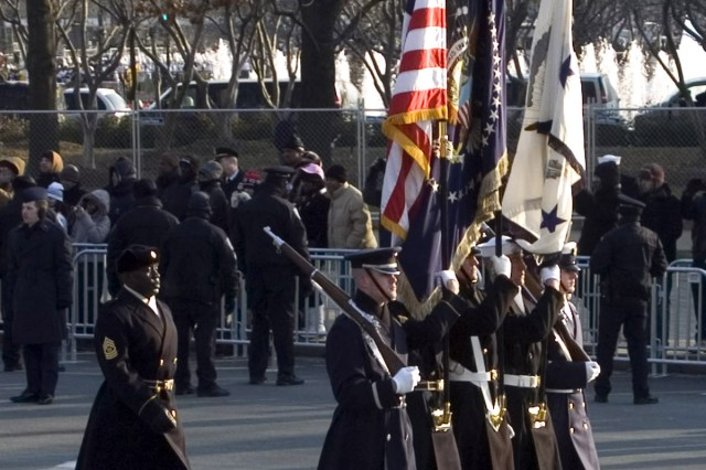 The Armed Forces Color Guard carries the American flag, the presidential flag, and the vice presidential flag in the inaugural parade as Old Guard Command Sergeant Major Russel McCray follows behind.