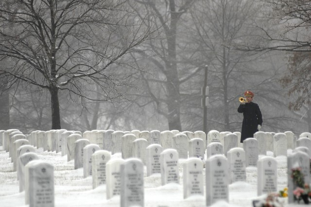 "A bugler from the U.S. Army Band ""Pershing's Own"" plays taps at the burial service Wednesday in Arlington National Cemetery for former Sgt. Maj. of the Army William G. Bainbridge."