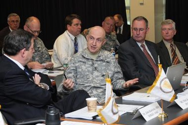 Senior Officer of PEO C3T, Maj. Gen. Nick Justice, emphasizes a point to John Kubricky, Director of Defense Research and Engineering Advanced Systems and Concepts. Michael Krieger, the Army Deputy Chief Information Officer/G6 and other attendees listen intently.