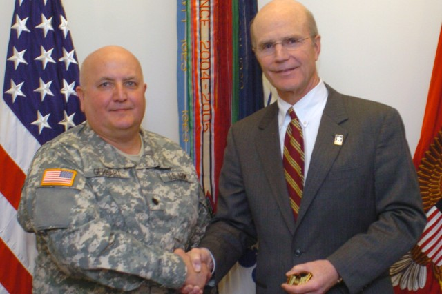 Lt. Col. Karl Gerhart, AMC G3/5 Current Operations, receives the Army Coin for Excellence from Secretary of the Army, Pete Geren Jan. 27 in recognition for his efforts in assisting in the rapid fielding of MRAP Gunner\'s Restraint Systems in Southwest Asia. The GRS dramatically improves Soldier survivability in MRAP incidents and can be directly attributed to saving lives in Iraq and Afghanistan.