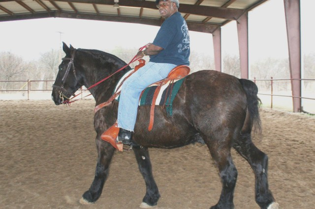 Retired Sgt. 1st Class Roger Clark takes a ride on Herb around the Fort Sam Houston Equestrian Center. A former wounded warrior himself, Clark is responsible for all of Herb\'s needs.