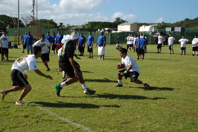 ALIAMANU MILITARY RESERVATION, Hawaii - A running back (center, forefront) attempts to evade the defensive line during a scrimmage with 12-17 year-olds at the 4th Annual Football Bash Clinic, Jan. 24.