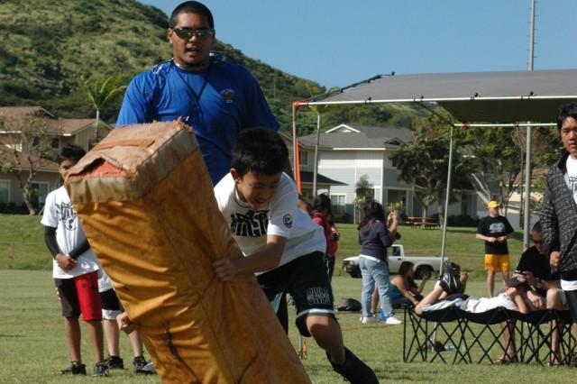 ALIAMANU MILITARY RESERVATION, Hawaii - Matthew Chang attacks the tackling bag while Warren Tauanuu, Stockton Lightning, provides pointers at the 4th Annual Football Bash Clinic, Jan. 24.