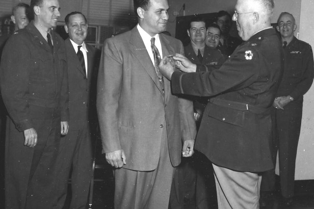 PICATINNY ARSENAL, N.J. -- Col. Harris presents the Decoration for Exceptional Civilian Service to Robert M. Schwartz Oct. 24, 1952. Schwartz is known as the man who moved Picatinny into the Atomic Age.