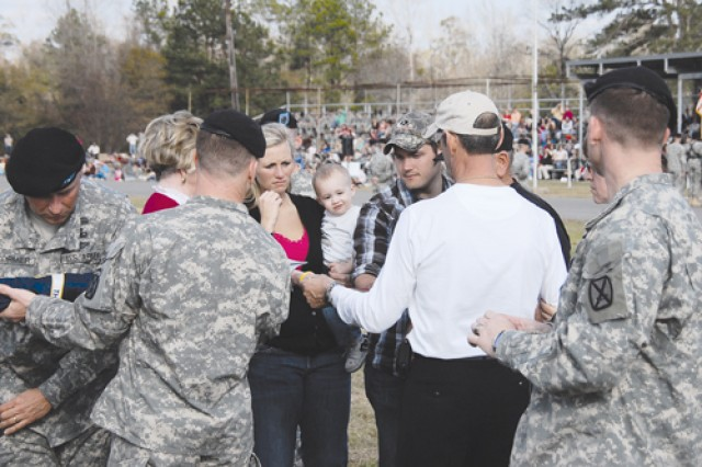 Gold Star Family members whose Soldiers were killed while serving with the 4th Brigade Combat Team, 10th Mountain Division, during its 14-month deployment to Iraq, assist in placing a battle streamer on the unit colors of the 2nd Battalion, 30th Infantry Regiment during a redeployment ceremony Jan. 23 on Fort Polk's Honor Field.