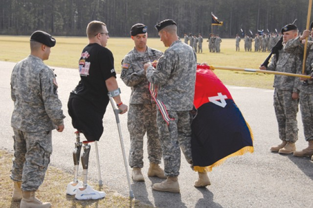 Sgt. Nathan Hunt, 4th Brigade Combat Team, 10th Mountain Division, who lost his legs in an attack in Baghdad April 28, 2008, the same day two other Soldiers in his unit were killed, helps Col. Mark Dewhurst (third from left), commander, 4th BCT, place the battle streamer earned by the unit's Soldiers on the guidon during a redeployment ceremony Jan. 23 on Fort Polk's Honor Field. The 4/10 was deployed for 14 months.
