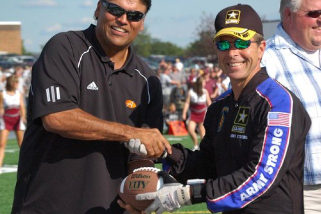 John Hart of Team Fastrax presents the game ball to NFL Hall of Fame player Anthony Munoz at the dedication of the new Lebanon High School football stadium in Lebanon, Ohio.