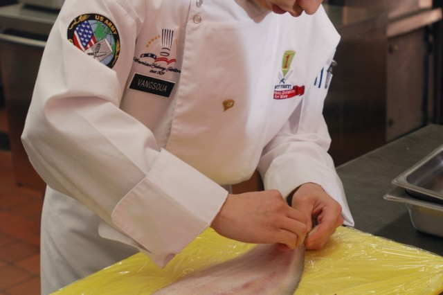 Spc. Thao Vangsoua prepares a sole fish Jan. 22 at the 1st Infantry Division culinary competition.  Both teams in the contest had to prepare one dish using sole for the appetizer.  1st ID Public Affairs Office Journalist, Spc. Cody Harding.