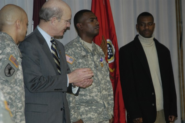 Secretary of the Army Pete Geren applauds Sgt. Justin Smith after awarding him the Purple Heart during a ceremony at Walter Reed Army Medical Center Jan. 30. Smith was injured June 6, 2007, while conducting route clearance operations in Pakitka Province, Afghanistan.