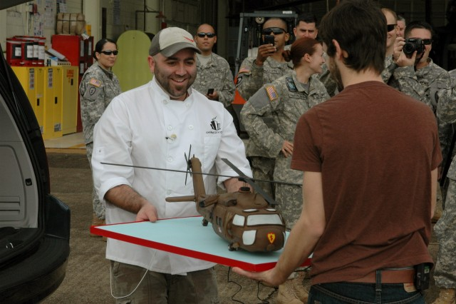 "Jeffrey ""Duff"" Goldman and Geoffrey Manthorne, stars of the Food Network show ""Ace of Cakes"", move the UH-60 Blackhawk cake to the Wheeler Army Airfield location for the ""Hero"" shot, Jan 29.  ""Ace of Cakes"" brought their show to Schofield Barracks to say thanks to Soldiers and family members with a unique piece of culinary art."
