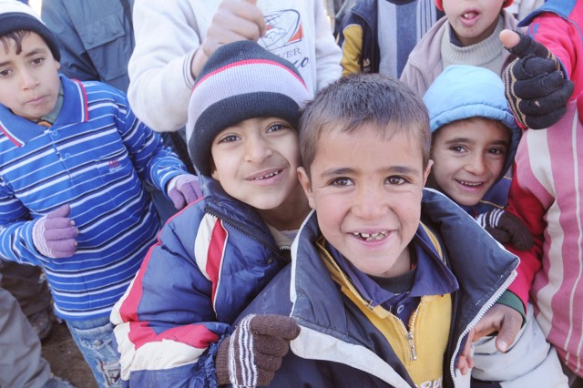 Children smile for the camera in the village of Atshiyana, Iraq Jan. 12. The children of the community were invited to a school opening in Kirkuk Province.