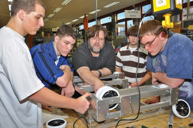 Members of the Wiesbaden High School Robotics team work with instructor Frank Pendzich on the robot's platform.