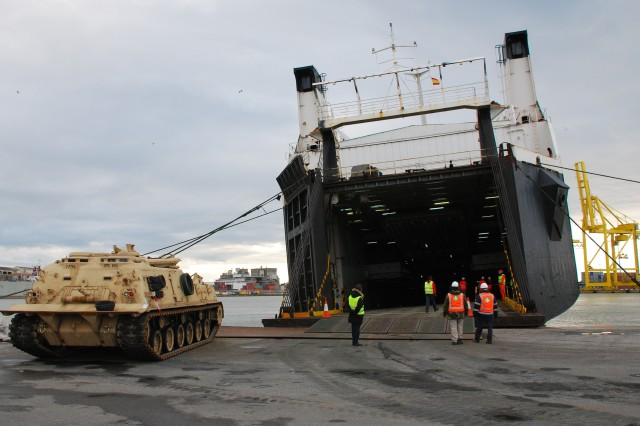 839th Transportation Bn. Employees unload tracked vehicles from a ship at the Livorno Port in Livorno, Italy.