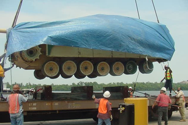 Stevedores at the Port of Beaumont, Texas, load an Abrams tank onto a DODX railcar fitted with special cribbing designed by 842nd Transportation Battalion's Ralph Cote. Cote's ingenuity has saved the Army thousands of dollars in transportation costs for damaged track vehicles that would otherwise be moved by truck.