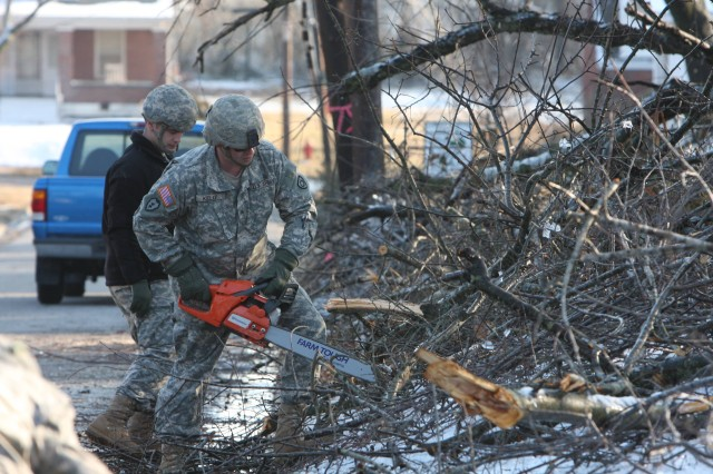 Sgt. Thomas Kelly and a fellow Soldier, both of Company A, 149th Brigade Support Battalion, form a team to clear branches lying near or across the streets of Mayfield, Ky., Jan. 30.