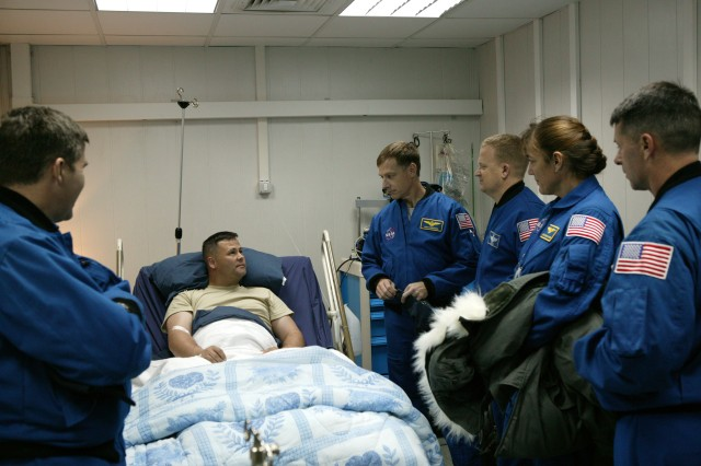 The crew visits a wounded Soldier at Manas Air Base, Kyrgyzstan. Pictured are (left to right): Stephen Bowen, a Soldier, Chris Ferguson, Eric Boe, Heidemarie Stefanyshyn-Piper and Shane Kimbrough.