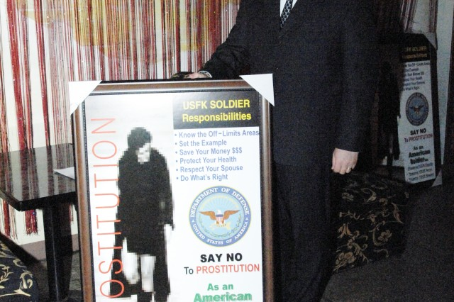 Ray Myers, USAG-RC DES director, stands next to new anti-prostitution and human trafficking poster during a meeting held in Bosundong, Dongducheon's entertainment area outside the USAG-Casey main gate. The posters were given to the club owners to display in their clubs to remind patrons to report any significant indicators of prostitution and human trafficking taking place.